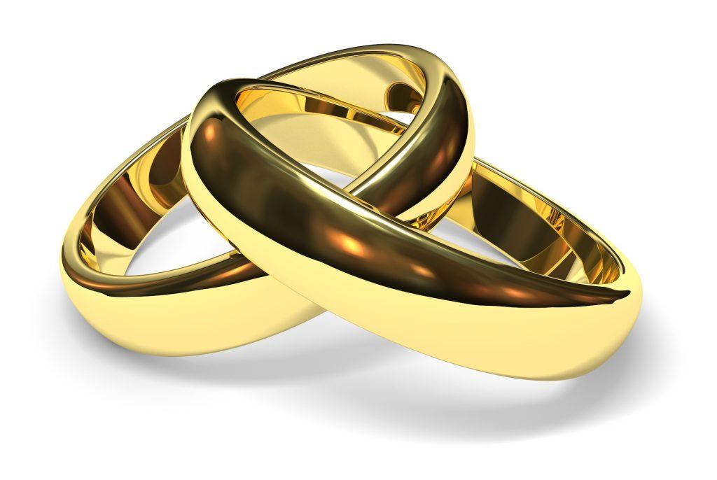 linked gold wedding rings on white background